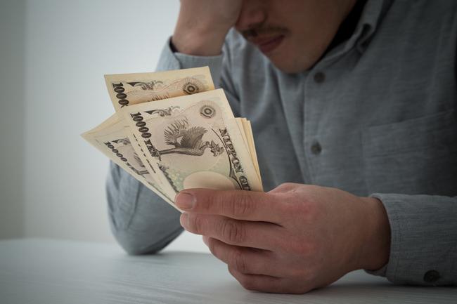 借金が払えないことに悩む男性